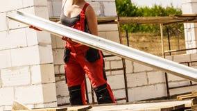 Φέρνοντας υδρορροή γυναικών στο εργοτάξιο οικοδομής στοκ φωτογραφία με δικαίωμα ελεύθερης χρήσης