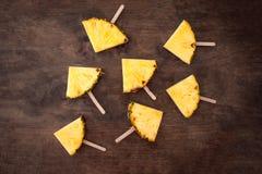 Φέτα ανανά popsicles σε ένα καφετί αγροτικό ξύλινο υπόβαθρο ΛΦ στοκ εικόνες με δικαίωμα ελεύθερης χρήσης