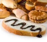 Φέτα εικόνας του άσπρου ψωμιού που ποτίζεται με την υγρά σοκολάτα και τα μπισκότα Στοκ Εικόνες
