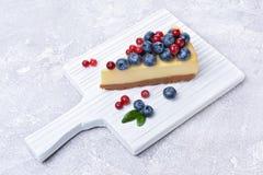 Φέτα κινηματογραφήσεων σε πρώτο πλάνο εύγευστο σπιτικό cheesecake με τα φρέσκα βακκίνια και τα τα βακκίνια στο λευκό ξύλινο τέμνο Στοκ Εικόνες