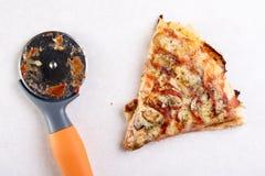 Φέτα πιτσών με το στρογγυλό μαχαίρι πιτσών στον άσπρο μαρμάρινο πίνακα υποβάθρου Στοκ Εικόνες