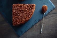 Φέτα του βαλμένου σε στρώσεις κέικ μελιού στο μαύρους από γραφίτη πίνακα και το κουταλάκι του γλυκού πλακών Τοπ όψη Ένα κομμάτι Ε Στοκ Εικόνες