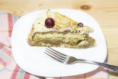 Φέτα του εύγευστου σπιτικού κέικ με την κρέμα καφέ που διακοσμείται από το κόκκινο σταφύλι και τα αχλάδια στο άσπρο πιάτο στον ξύ Στοκ Εικόνες