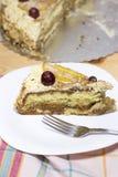 Φέτα του εύγευστου σπιτικού κέικ με την κρέμα καφέ που διακοσμείται από το κόκκινο σταφύλι και τα αχλάδια στο άσπρο πιάτο στον ξύ Στοκ Φωτογραφία