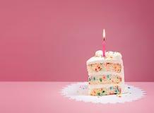 Φέτα του κέικ γενεθλίων με το κερί στο ροζ Στοκ Εικόνες