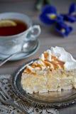 Φέτα του κέικ μαρέγκας και ένα φλυτζάνι του τσαγιού και της ίριδας στοκ εικόνες με δικαίωμα ελεύθερης χρήσης
