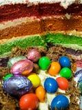 Φέτα του κέικ στο χρόνο Πάσχας που παρουσιάζει τα χρωματισμένα στρώματα και αυγά Στοκ Φωτογραφίες