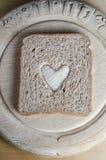 Φέτα του καφετιού ψωμιού με την άσπρη καρδιά στον εκλεκτής ποιότητας ξύλινο πίνακα Στοκ εικόνα με δικαίωμα ελεύθερης χρήσης