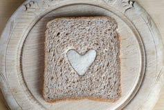 Φέτα του καφετιού ψωμιού με την άσπρη καρδιά στον εκλεκτής ποιότητας πίνακα ψωμιού Στοκ Φωτογραφίες