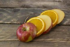Φέτα του κόκκινων μήλου και του πορτοκαλιού στις ξύλινες γέφυρες Στοκ φωτογραφίες με δικαίωμα ελεύθερης χρήσης