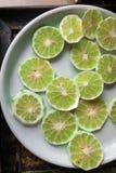 Φέτα του ξεφλουδισμένου πράσινου φρέσκου ασβέστη στο άσπρο πιάτο Στοκ εικόνες με δικαίωμα ελεύθερης χρήσης