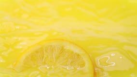 Φέτα του πορτοκαλιού που περιέρχεται στο χυμό από πορτοκάλι απόθεμα βίντεο