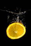 Φέτα του πορτοκαλιού στο νερό στο Μαύρο Στοκ Φωτογραφίες