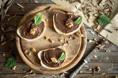 Φέτα του ψωμιού με την κρέμα και τα καρύδια σοκολάτας Σοκολάτα που διαδίδεται με το μαχαίρι Στοκ Εικόνες
