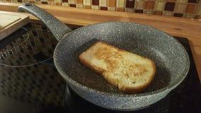 Φέτα του ψωμιού που ψήνεται σε μια παν κουζίνα στοκ εικόνες