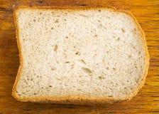 Φέτα του ψωμιού σε ένα παλαιό τέμνον υπόβαθρο πινάκων Στοκ φωτογραφία με δικαίωμα ελεύθερης χρήσης