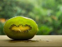 Φέτα των φρούτων ακτινίδιων που στέκεται σε έναν ξύλινο πίνακα με το θολωμένο υπόβαθρο στοκ εικόνα