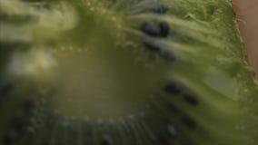 Φέτα φρούτων ακτινίδιων στο ακραίο στενό επάνω μήκος σε πόδηα αποθεμάτων Μια φέτα των φρούτων ακτινίδιων μακρο στενό σε επάνω με  απόθεμα βίντεο
