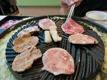 Φέτα χοιρινού κρέατος σχαρών στο καυτό BBQ τηγάνι, χρόνος οικογενειακών γευμάτων, χοιρινό κρέας chopstick, έτοιμο να φάει Στοκ Εικόνα