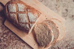 Φέτα ψωμιού σε έναν ξύλινο πίνακα Φρέσκια φραντζόλα σίτου Στοκ Εικόνα