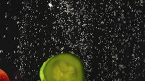 Φέτες αγγουριών που περιέρχονται στο νερό με την ντομάτα στο μαύρο υπόβαθρο Φρέσκο λαχανικό στο νερό με τις φυσαλίδες E απόθεμα βίντεο