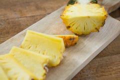 Φέτες και διχοτομημένος ανανάς που κρατιούνται στον τεμαχίζοντας πίνακα στοκ φωτογραφία με δικαίωμα ελεύθερης χρήσης