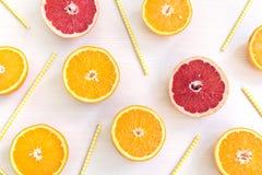 Φέτες πορτοκαλιών και γκρέιπφρουτ με τα κίτρινα άχυρα που βρίσκονται σε ένα ελαφρύ υπόβαθρο στοκ εικόνες με δικαίωμα ελεύθερης χρήσης