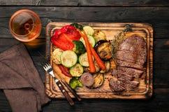 Φέτες της μπριζόλας βόειου κρέατος με τα ψημένα στη σχάρα λαχανικά και το κονιάκ Στοκ φωτογραφία με δικαίωμα ελεύθερης χρήσης
