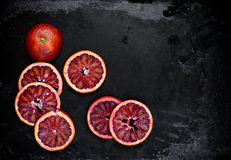 Φέτες του κόκκινου πορτοκαλιού σε ένα μαύρο μεταλλικό υπόβαθρο Στοκ φωτογραφία με δικαίωμα ελεύθερης χρήσης