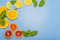 Φέτες του λεμονιού, του πορτοκαλιού και ενός κλαδάκι της μέντας σε ένα μπλε υπόβαθρο Στοκ Εικόνες