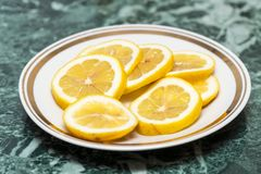 Φέτες του λεμονιού στο άσπρο πιάτο Στοκ Φωτογραφία