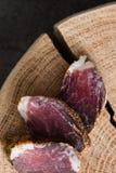 Φέτες του ξηρού κρέατος στην ξύλινη περικοπή στο σκοτεινό αγροτικό υπόβαθρο Στοκ Φωτογραφία
