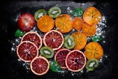Φέτες του πορτοκαλιού αίματος, ακτινίδιο, persimmon και με την κονιοποιημένη ζάχαρη Στοκ Εικόνα