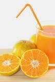 Φέτες του πορτοκαλιού με το χυμό από πορτοκάλι φρέσκο στο γυαλί Στοκ Εικόνα