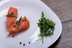 Φέτες του σολομού με το arugula σε ένα άσπρο πιάτο Στοκ Φωτογραφία