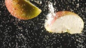 Φέτες του φρέσκου ραντίσματος μήλων στο νερό στο μαύρο υπόβαθρο Μειωμένοι νωποί καρποί στο νερό E o φιλμ μικρού μήκους