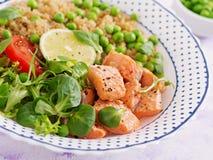 Φέτες του ψημένου στη σχάρα σολομού, quinoa, των πράσινων μπιζελιών, των φύλλων ντοματών, ασβέστη και μαρουλιού Στοκ Εικόνα