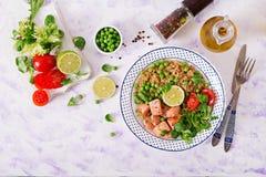 Φέτες του ψημένου στη σχάρα σολομού, quinoa, των πράσινων μπιζελιών, των φύλλων ντοματών, ασβέστη και μαρουλιού Στοκ εικόνα με δικαίωμα ελεύθερης χρήσης