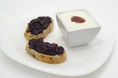 Φέτες του ψωμιού με τη μαρμελάδα και φλυτζάνι της μαρμελάδας Στοκ φωτογραφία με δικαίωμα ελεύθερης χρήσης