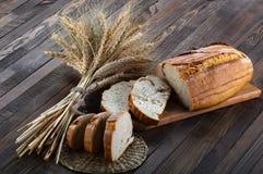 Φέτες του ψωμιού σε έναν τέμνοντα πίνακα και τα αυτιά του σίτου στο ξύλο στοκ εικόνες
