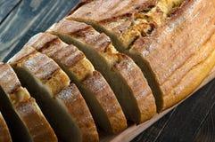 Φέτες του ψωμιού σε έναν τέμνοντα πίνακα σε ένα ξύλινο υπόβαθρο Στοκ φωτογραφία με δικαίωμα ελεύθερης χρήσης