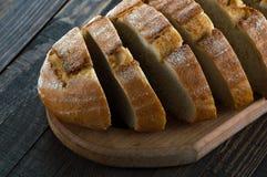 Φέτες του ψωμιού σε έναν τέμνοντα πίνακα Στοκ Φωτογραφία
