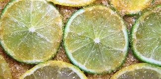 Φέτες των ασβεστών και των λεμονιών που αναμιγνύονται με τη ζάχαρη καλάμων στοκ εικόνα με δικαίωμα ελεύθερης χρήσης