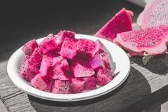 Φέτες των κόκκινων φρούτων δράκων στο πιάτο με το υπόβαθρο επίδρασης Bokeh ή θαμπάδων στοκ φωτογραφία με δικαίωμα ελεύθερης χρήσης