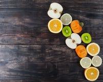 Φέτες των υγιών φρούτων στον ξύλινο πίνακα με το διάστημα αντιγράφων Στοκ Εικόνες