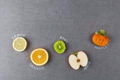 Φέτες των φρούτων με τις ετικέτες στην πέτρα Στοκ φωτογραφία με δικαίωμα ελεύθερης χρήσης
