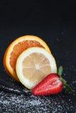 Φέτες των φρούτων σε ένα σκοτεινό υπόβαθρο Στοκ εικόνα με δικαίωμα ελεύθερης χρήσης