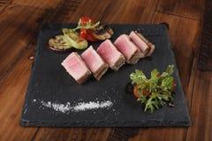 Φέτες λωρίδων τόνου με τη σαλάτα στην γκρίζα πλάκα Στοκ Εικόνες