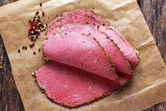 Φέτες pastrami βόειου κρέατος ψητού Peppered σε χαρτί με τα σιτάρια του χρωματισμένου πιπεριού Στοκ εικόνες με δικαίωμα ελεύθερης χρήσης
