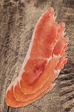 Φέτες Prosciutto στο παλαιό ξύλινο υπόβαθρο Στοκ Φωτογραφία